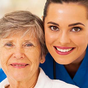 Smiling nurse with an elderly patient